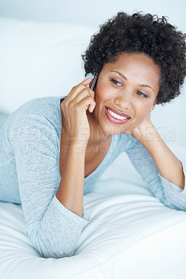 Buy stock photo African American woman talking on mobile phone while lying on couch