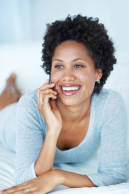 Buy stock photo Beautiful young woman smiling while talking on mobile phone on couch
