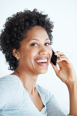 Buy stock photo Closeup of cheerful young woman talking on mobile phone over white background