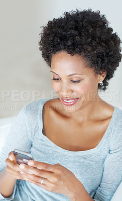Buy stock photo Attractive woman reading text message on mobile phone at home