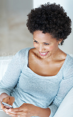 Buy stock photo Smiling African American woman texting on couch