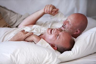 Buy stock photo Playful homosexual couple frolicking on their bed of white linen