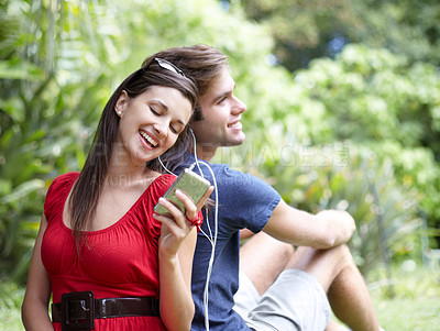 Buy stock photo Young couple shares a pair of earphones in the park
