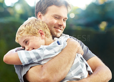 Buy stock photo Shot of a smiling father hugging his son outside