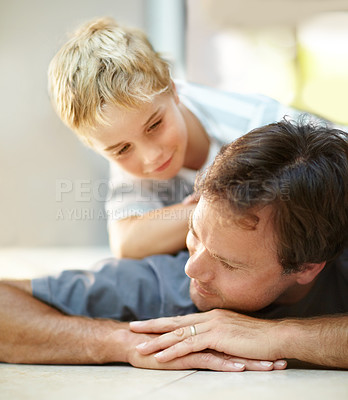 Buy stock photo Young boy lying on his fathers back and looking at him in affection
