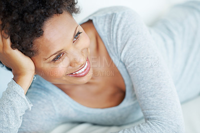 Buy stock photo Closeup of attractive African American woman daydreaming while lying on couch