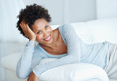 Buy stock photo Portrait of beautiful young woman smiling while resting on comfortable sofa