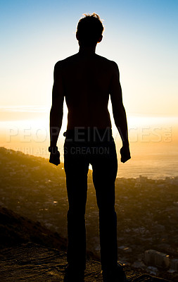 Buy stock photo Silhouette of a young man staring into the sunset.