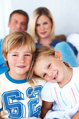 Buy stock photo Portrait of cute little girl resting on brother's shoulder with parents in background