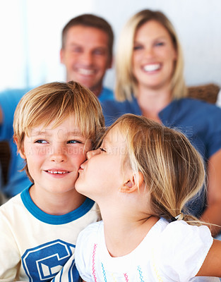 Buy stock photo Cute little girl kissing brother with parents in background