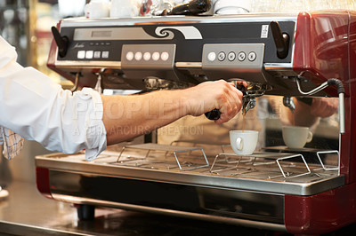 Buy stock photo Male making a fresh cup of coffee in a cafe using a professional coffee machine