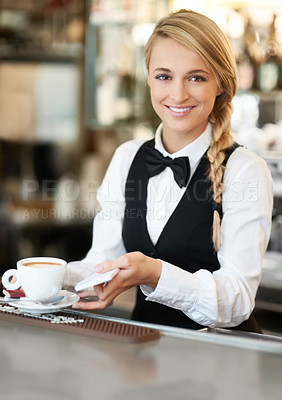 Buy stock photo Young pretty waitress preparing to serve a delicious cup of coffee to a customer