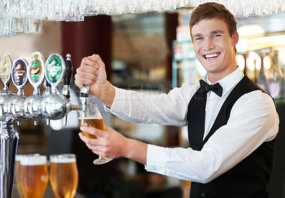 Buy stock photo Happy young barman preparing beer on tap with a smile