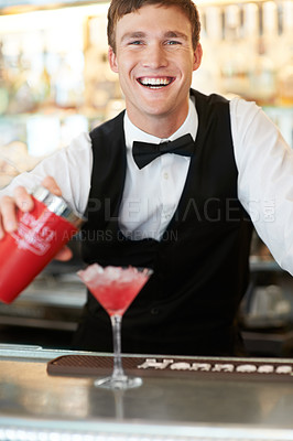 Buy stock photo Young handsome barman laughing and smiling while wipping up a delicous and tasty cocktail