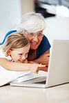 Girl using laptop with grandmother
