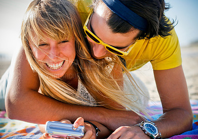 Buy stock photo Cute couple playing around giggling on the beach