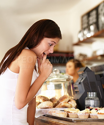 Buy stock photo Pretty young girl looking down at rows of cupcakes in a bakery and trying to make a decision