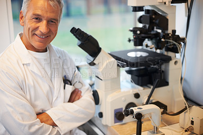 Buy stock photo Portrait of smiling mature male scientist in laboratory with a microscope