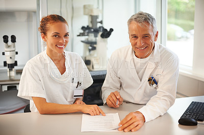 Buy stock photo Two researchers working on test results and smiling in lab