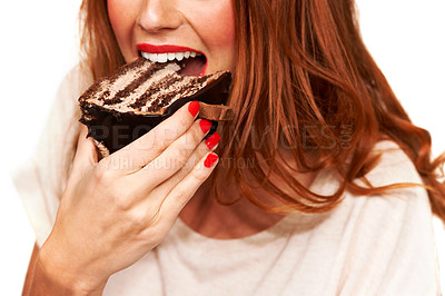 Buy stock photo Cropped closeup of a young woman taking a bite from a piece of cake