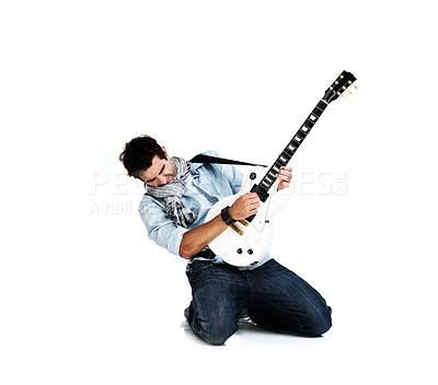 Buy stock photo Male guitarist kneeling and playing his guitar passionately, isolated on white - copyspace