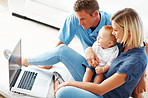 Couple using laptop with baby