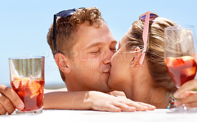Buy stock photo A young couple kissing passionately in the hot summer sun