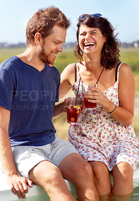 Buy stock photo A young couple toast each other on a summer's day