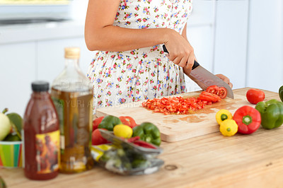Buy stock photo Cropped image of a woman chopping a tomato for a meal in the kitchen
