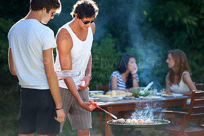 Buy stock photo Young guys barbequing meat on the grill outdoors - Lifestyle