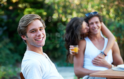Buy stock photo Positive young man at a lunch with a group of friends - portrait