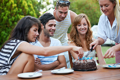 Buy stock photo Happy young teen friends celebrating someone's birthday and cutting some birthday cake