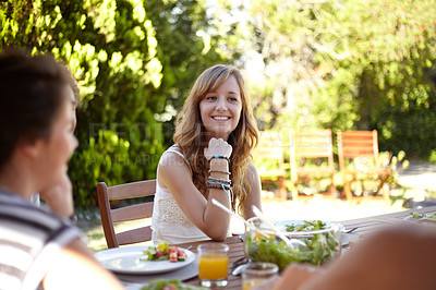 Buy stock photo Smiling young woman at a lunch with a group of friends