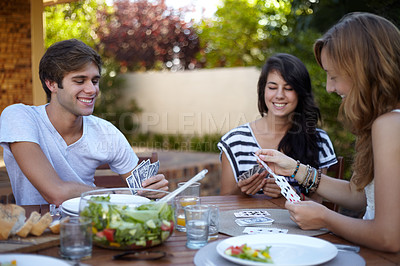 Buy stock photo Smiling young people at a lunch with a group of friends and playing a game of cards