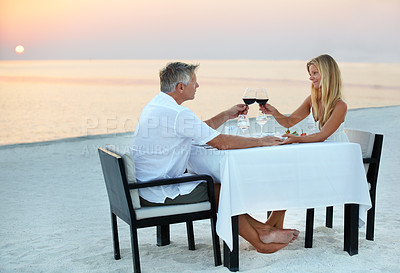 Buy stock photo Shot of a mature couple enjoying a romantic dinner on the beach