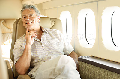 Buy stock photo Portrait of a handsome senior man sitting in an airplane with a smile