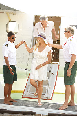 Buy stock photo Mature couple stepping off an airplane in a foreign destination