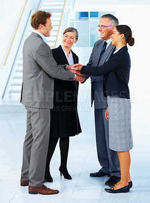 Buy stock photo Handshake and teamwork. A group of businesspeople shaking hands in a light and modern office.