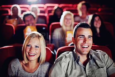 Buy stock photo A couple laughing and watching a movie together at the cinema
