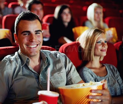 Buy stock photo A portrait of a happy young man holding a refreshment and popcorn in a cinema while with his girlfriend