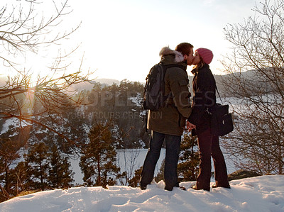 Buy stock photo Two lovers kissing as the sun sets on a snowy landscape