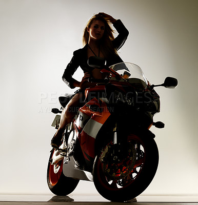 Buy stock photo Stunning young woman in a bikini and leather jacket sitting on a motorcycle with her hands above her head