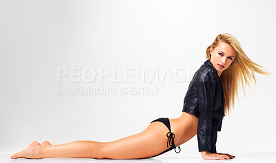 Buy stock photo Studio shot of a sexy young woman posing in a leather jacket and bikini