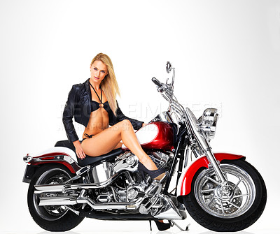Buy stock photo Studio portrait of a sexy young woman in a leather jacket and bikini sitting on a motorbike