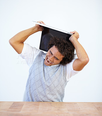 Buy stock photo Frustrated businessman about to smash his laptop