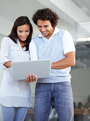 Buy stock photo Two young entrepreneurs working on a laptop together