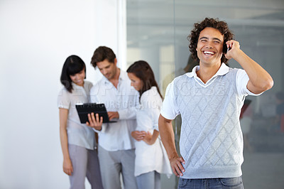 Buy stock photo A smiling entrepreneur taking a cellphone call while colleagues have a discussion in the background