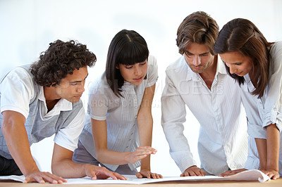 Buy stock photo A group of architects looking over some blueprints