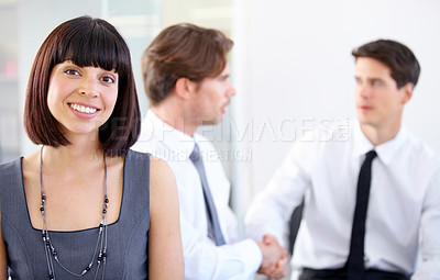 Buy stock photo Portrait of a young businesswoman smiling at the camera - blurred colleagues in the background
