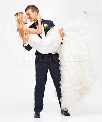Buy stock photo Handsome young groom holding his bride as they get ready to kiss